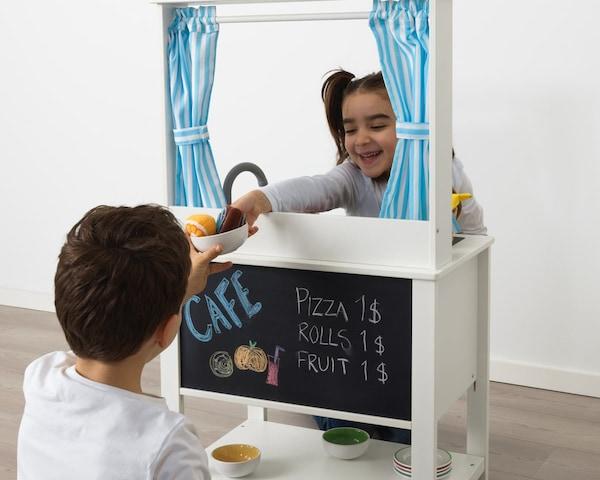 Дети играют в кафе, используя игрушечную кухню для детской