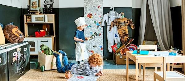 Deti sa hrajú v izbe s dvomi malými stolmi a stoličkami, tabuľou, miniatúrnou kuchyňou a vlajkami.