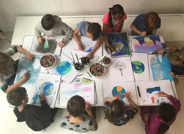 Děti sedí kolem stolu a kreslí obrázky zeměkoule