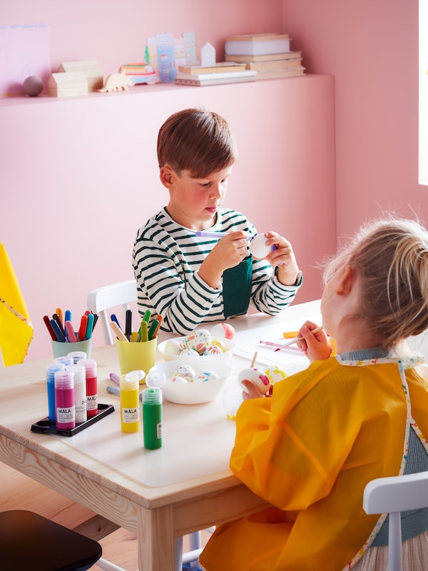 Děti si hrají u stolu ze světlého dřeva, na stole mají pastelky a další výtvarné potřeby.