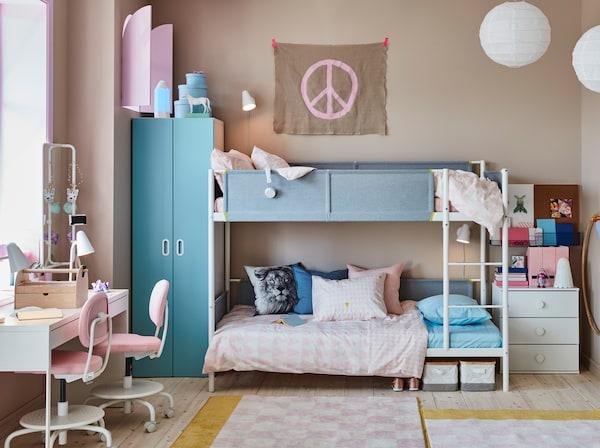 Detská izba s poschodovou posteľou s posteľnými obliečkami a skriňou, komodou, stolom a stoličkami.
