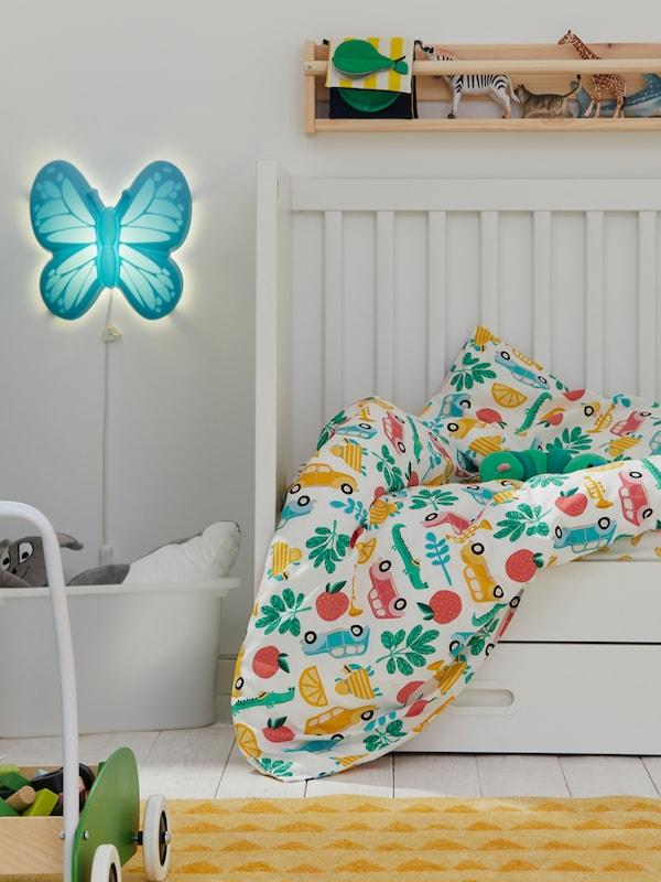 Dětská postýlka se zásuvkami STUVA/FRITIDS a barevné povlečení RÖRANDE. Poblíž je na stěně nástěnná lampa LED UPPLYST.