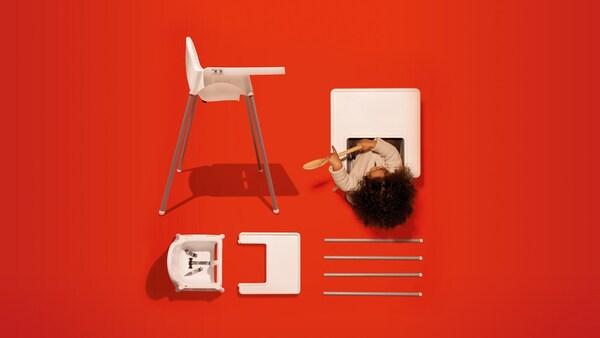 Dětská vysoká židle s podnosem v bílém provedení, dítě hrající si se lžící. Na boku části další židle na červeném pozadí.