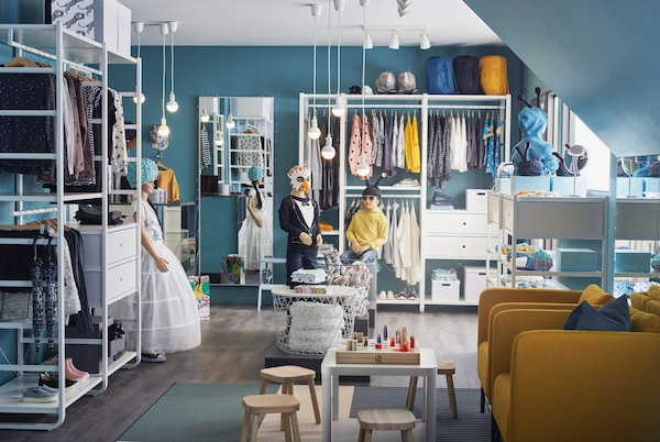 Детский магазин одежды с синими стенами, деревянным полом и белыми открытыми и закрытыми полками.
