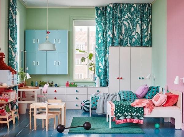 Dětský pokoj s bílými šatními skříněmi a komodami, dvěma postelovými rámy, zelený koberec a modrými nástěnnými skříňkami.