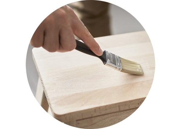 Dettaglio di un pennello in mano a una persona che sta dipingendo uno sgabello.