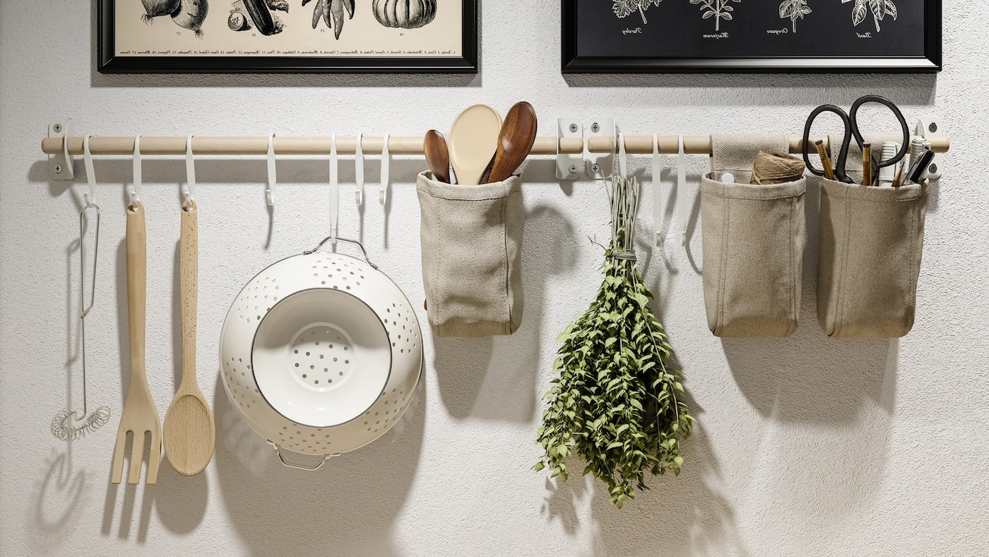 Deux affiches encadrées et des rails en bouleau NEREBY sur un mur blanc, avec des ustensiles de cuisine sur des crochets blancs et dans des récipients suspendus.