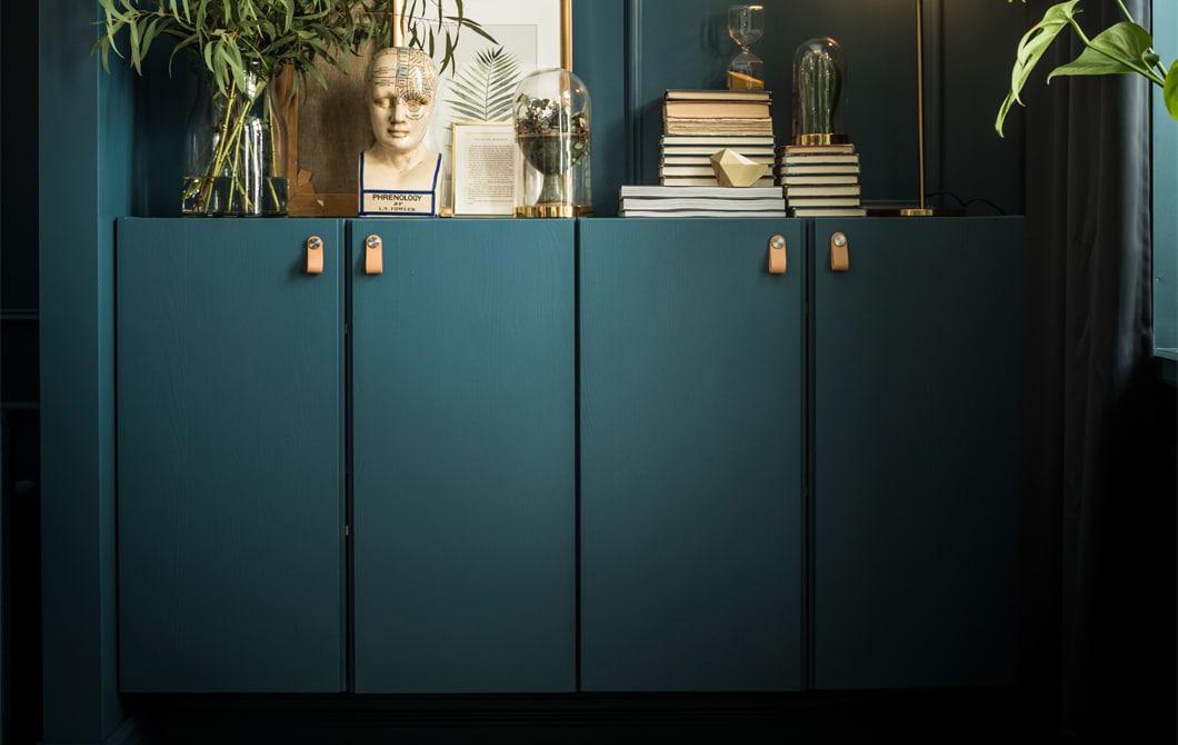 Deux armoires IVAR peintes de la même couleur que le mur accueillent livres, œuvres d'art, plantes et même une lampe.