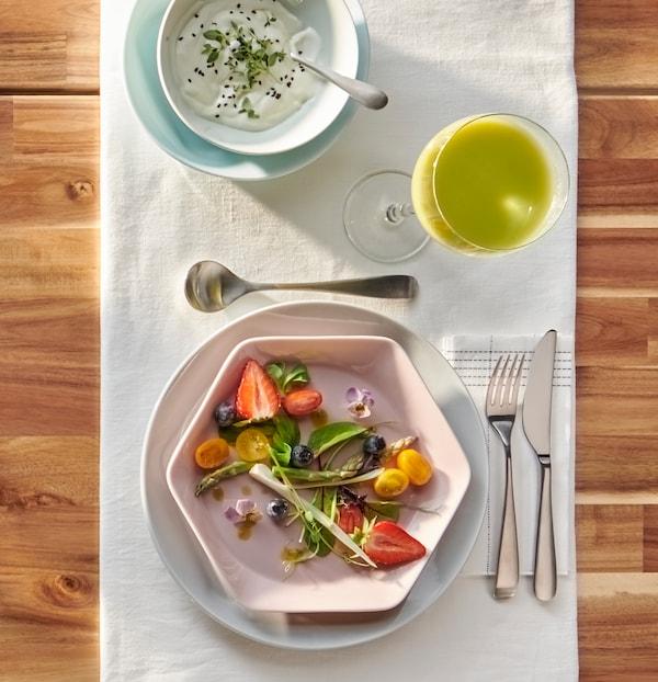 Deux assiettes rondes grises et bleu clair, bol blanc et assiette hexagonale rose FORMIDABEL avec salade estivale.