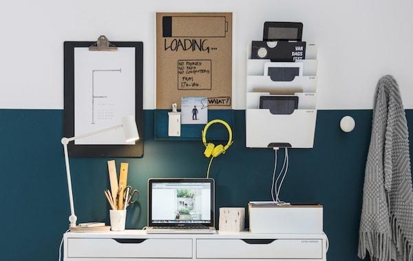 Deux boîtes de gestion de câbles posées sur un bureau placé devant un mur doté d'un range-revues composent cet aménagement de poste de charge central.