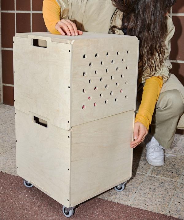 Deux boîtes de rangement de forme cubique en contreplaqué, empilées l'une sur l'autre. La boîte du bas est munie de roulettes.