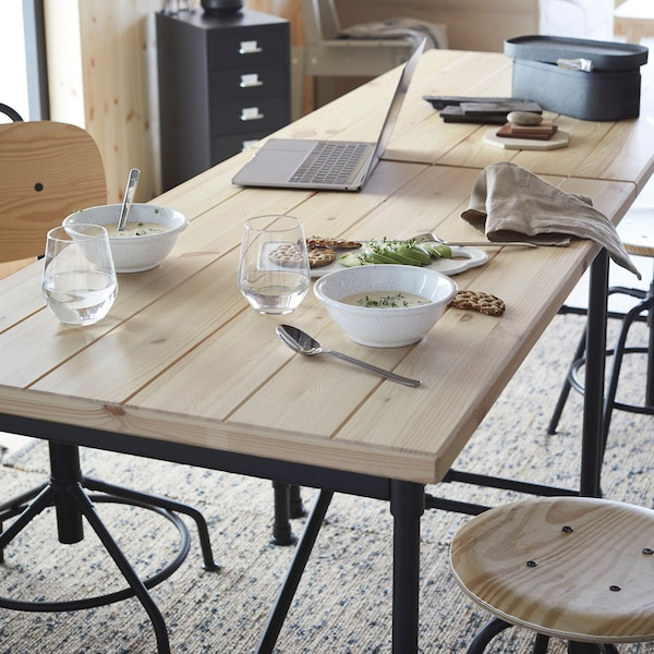 Deux bureaux en pin utilisés comme une table à manger, avec un ordinateur portable en arrière-plan.
