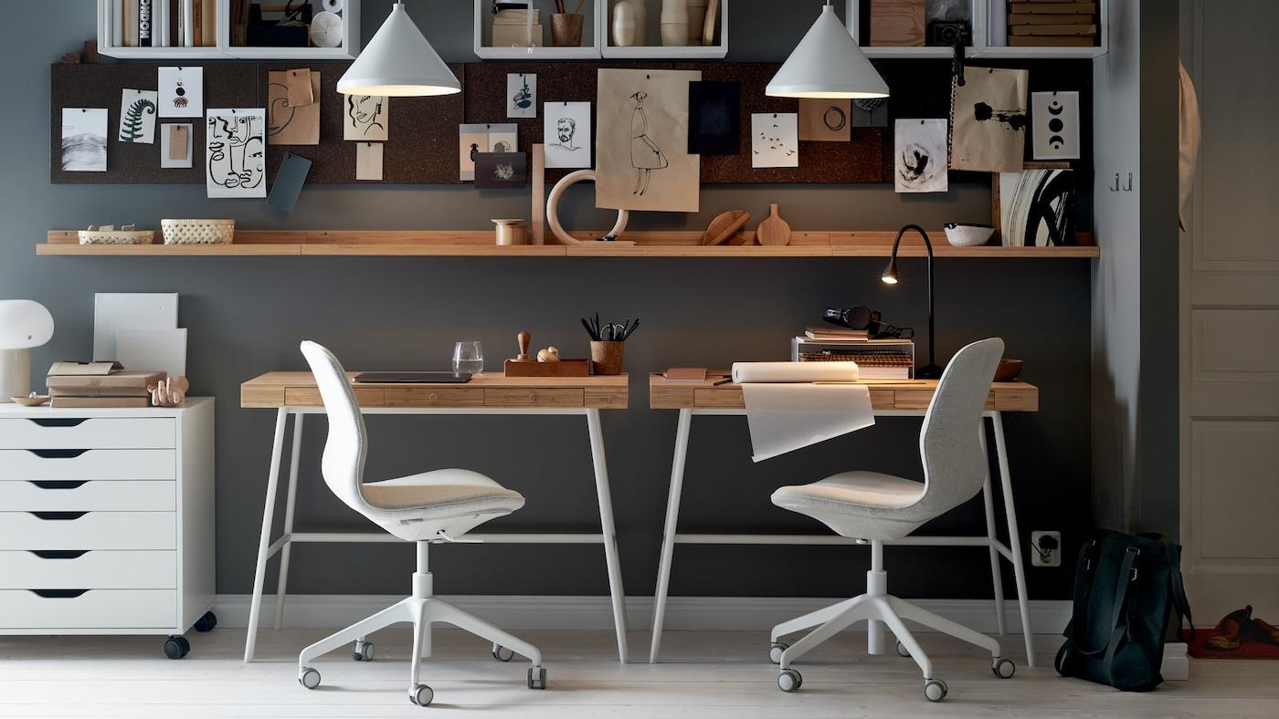 Deux bureaux LILLÅSEN contre un mur, chaises de bureau et caisson à tiroirs blanc, étagères, tableaux d'affichage et deux suspensions blanches.