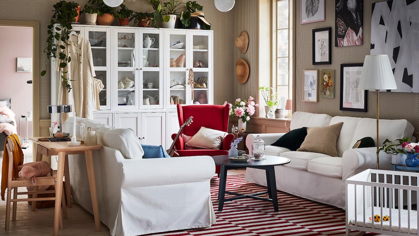 Deux canapés EKTORP sont placés l'un en face de l'autre dans un séjour blanc et rouge moderne et traditionnel à la fois.