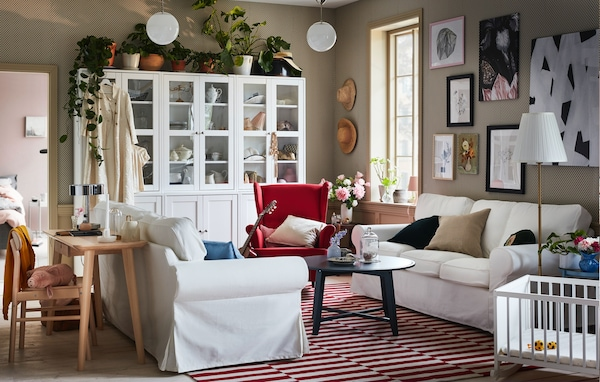 Deux canapés EKTORP sont placés l'un en face de l'autre dans un salon blanc et rouge moderne et traditionnel à la fois.