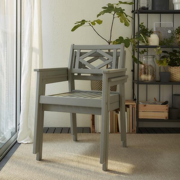 Deux chaises à accoudoirs grises empilées, sur un tapis beige, devant des étagères grises et des plantes vertes.