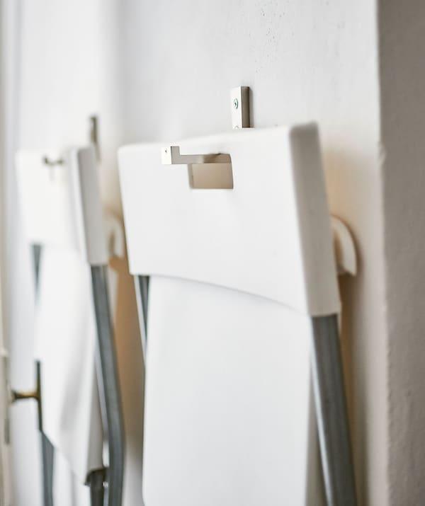 Deux chaises pliantes blanches accrochées au mur.