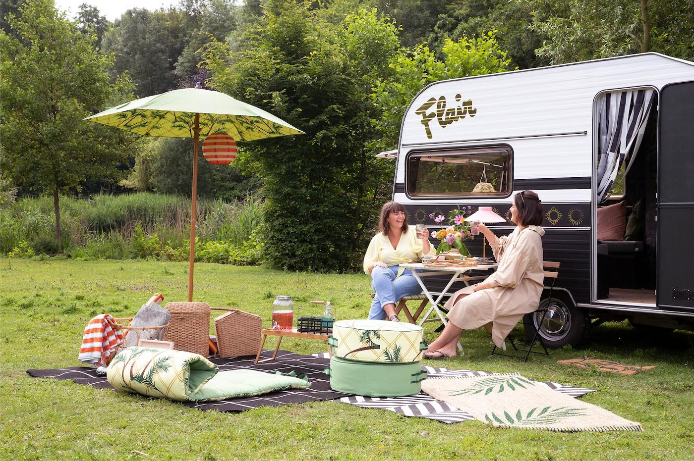 deux dames sur une terrasse devant une caravane dans la nature