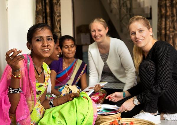 Deux designers IKEA assises avec les artisanes indiens, discutant une collection qu'elles sont en train de co-créer.