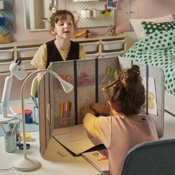 Deux écolières assises à leur propre bureau en vis-à-vis, avec un séparateur de bureau entre elles, dans une chambre d'enfants.