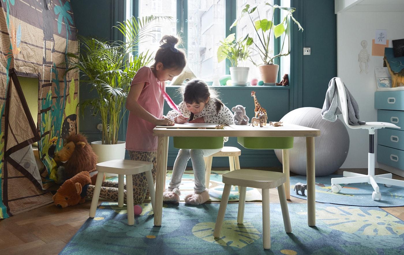 Deux enfants en train de dessiner à une table pour enfants, dans une salle de jeu.