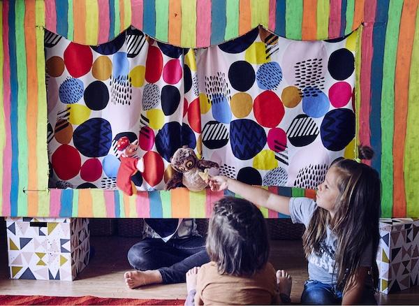 Deux enfants en train de regarder un vieux hibou dans le théâtre de marionnettes pendant qu'un troisième enfant est assis en tailleur derrière le rideau.