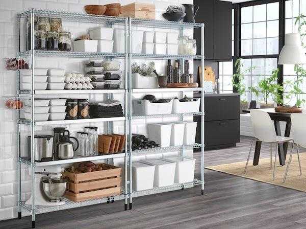 Deux étagères en acier galvanisé contre un mur blanc avec cuisine gris foncée dans le fond.