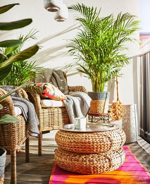 Deux fauteuils en rotin, deux poufs empilés faisant office de table, plantes et tapis aux couleurs vives trouvent place au balcon.