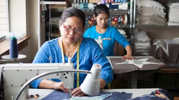 Deux femmes assemblant des chutes de tissus IKEA à Open Arms, une base d'entreprenariat au Texas qui propose de l'emploi aux femmes réfugiées.