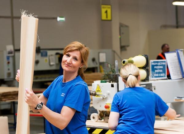 Deux femmes dans une usine produisant des meubles IKEA, dont l'une tient un panneau latéral en plaqué bouleau.