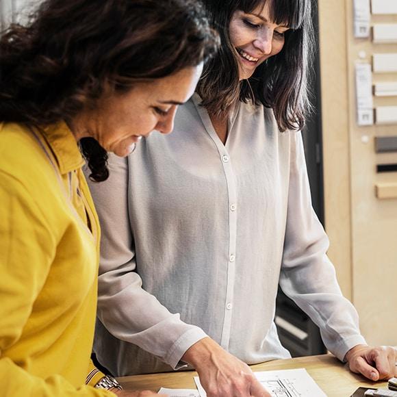 Deux femmes, dont une vendeuse IKEA, en train de regarder des plans