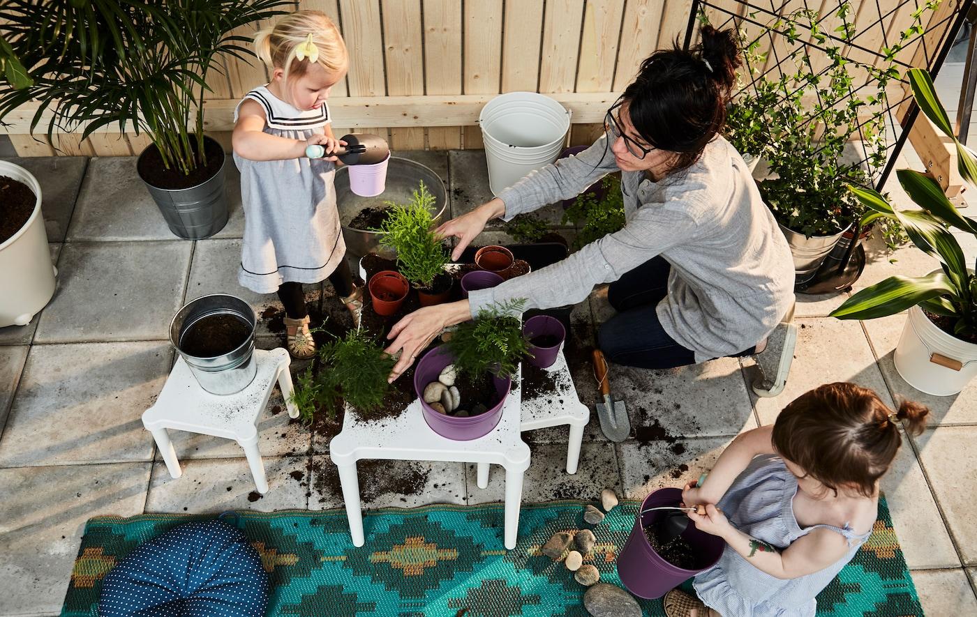 Deux fillettes en bas âge et un parent en train de mettre du terreau dans des cache-pots