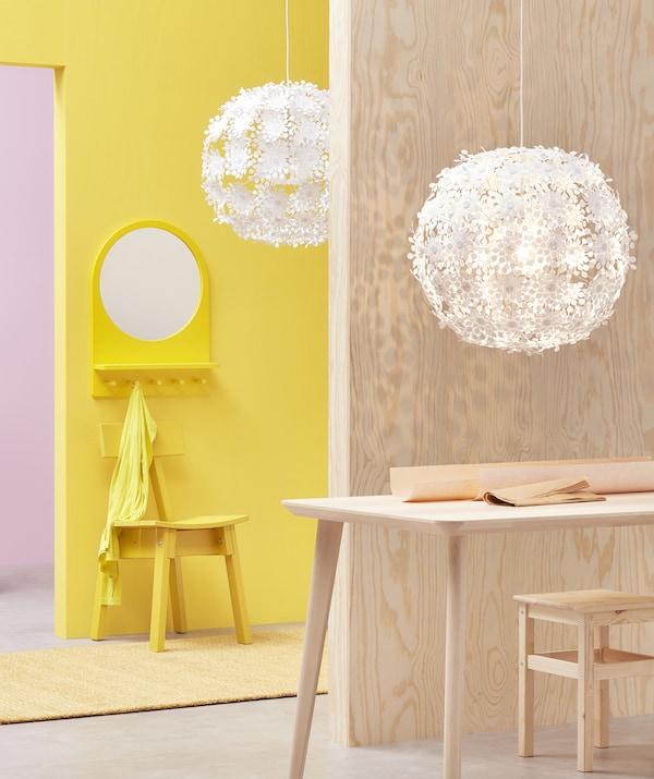 Deux grandes suspensions blanches ornées de motifs floraux, accrochées dans une pièce rose et jaune revêtue de bois clair.