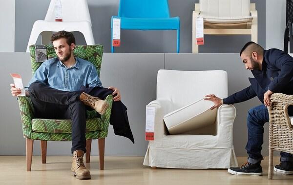 Deux hommes assis dans des fauteuils dans le département séjours IKEA. L'un lit l'étiquette de prix, l'autre examine un coussin d'assise.