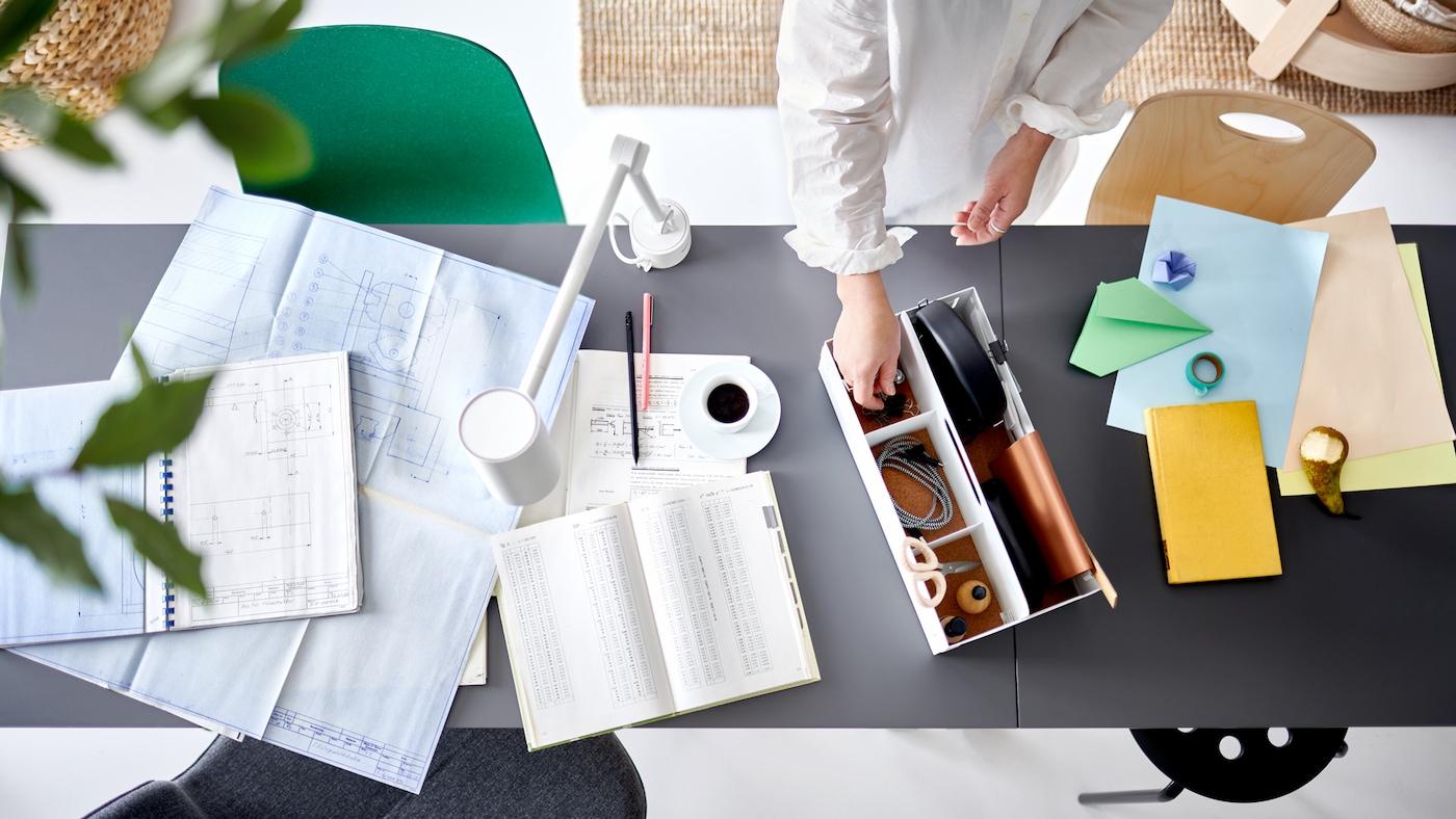 Deux mains prennent un objet dans un organiseur de bureau blanc sur deux plateaux de table joints où sont posés des documents de travail et une lampe de bureau blanche.