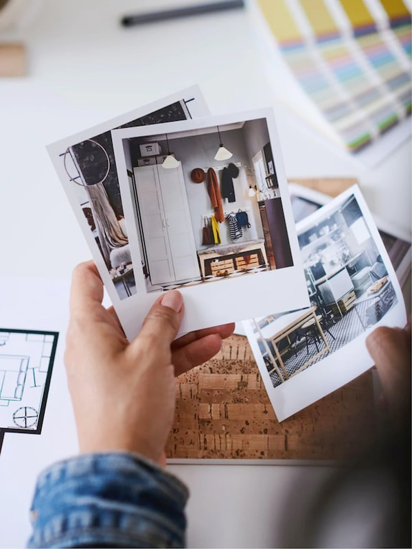 Deux mains tiennent un certain nombre de photos avec des propositions d'aménagement intérieur, à côté d'un nuancier et d'un plan d'aménagement. Shopping chez IKEA: toutes les possibilités.