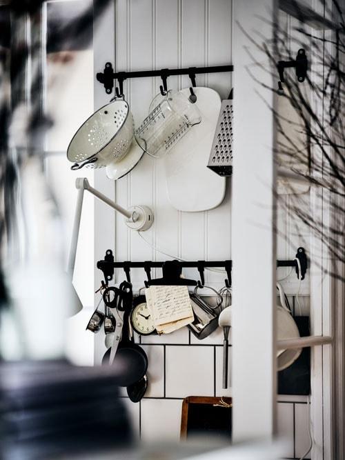 Deux rails HULTARP noirs avec des crochets fixés à un mur lambrissé blanc où sont accrochés des ustensiles de cuisine, comme une passoire et une râpe.