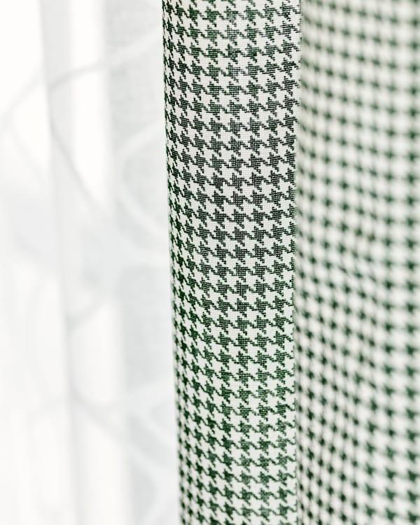 Deux rideaux en tissu pendus côte à côte, l'un en coton blanc translucide, l'autre à carreaux vert et blanc.