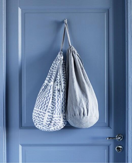 Deux sacs à lessive en tissu, aux motifs différents, accrochés au dos de la porte.