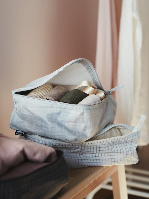 Deux sacs à vêtements RENSARE de couleurs claires et un de couleur foncée sont posés entrouverts sur une desserte, révélant des vêtements bienpliés.