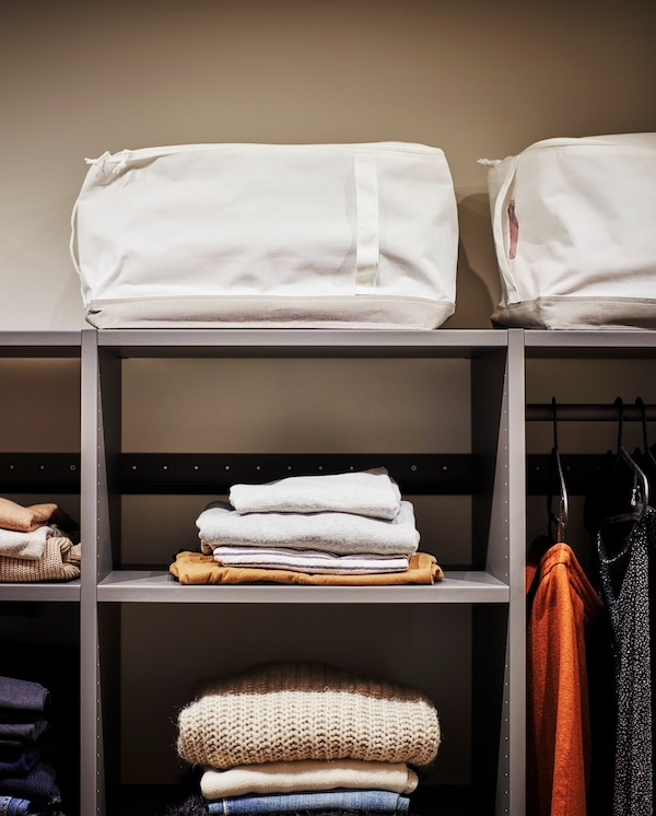 Deux sacs de rangement blanc/beige avec poignées posés au-dessus d'une penderie ouverte grise, pour ranger les affaires de saison.