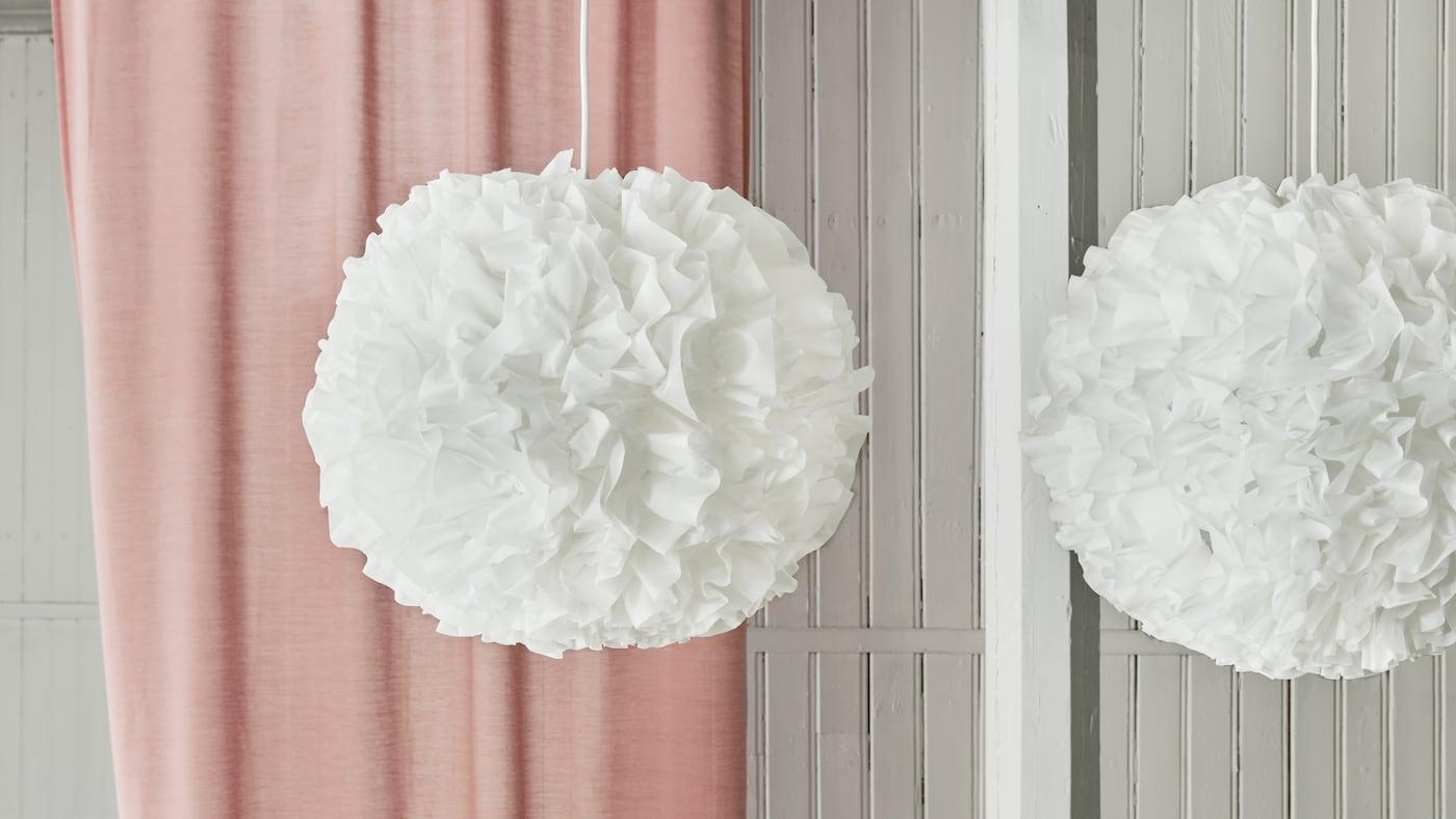 Deux suspensions VINDKAST éteintes, avec une suspension blanche à froufrous en forme de pompons devant un rideau rose.