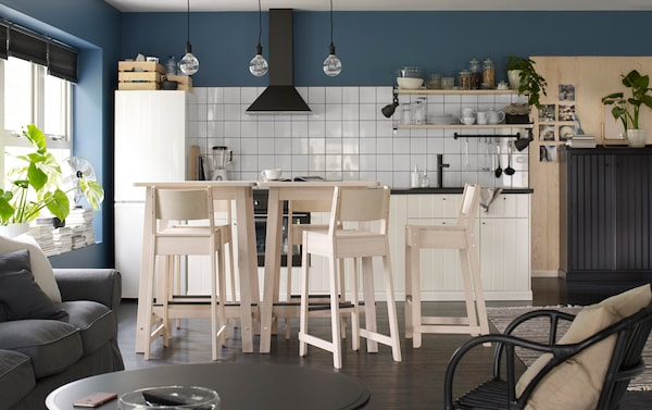 Deux tables de bar et cinq tabourets de bar en bouleau dans une cuisine de couleur bleue, blanche et bois clair.