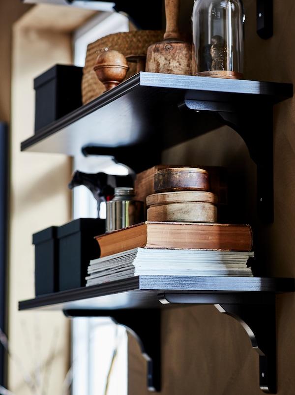 Deux tablettes murales brunes/noires BERGSHULT/RAMSHULT sur lesquelles sont rangés des livres, des boîtes et des objets décoratifs.