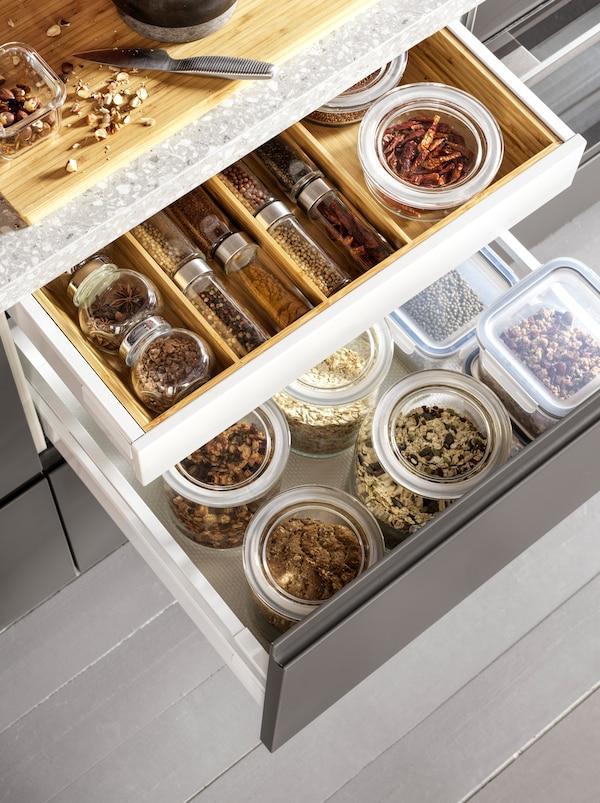 Deux tiroirs de cuisine ouverts avec des contenants en verre IKEA365+ remplis de grains et épices parfaitement disposées dans un range-couverts en bois.