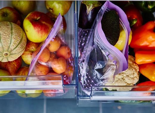 Deux tiroirs ouverts remplis de fruits et de légumes bien rangés.