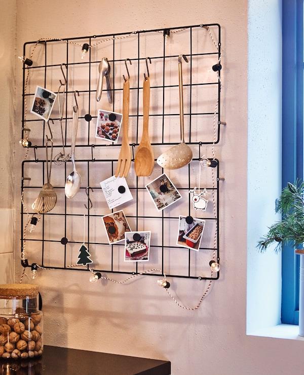 Deux treillis métalliques accrochés au mur d'une cuisine et portant des ustensiles de cuisine des fiches recettes et des objets décoratifs.