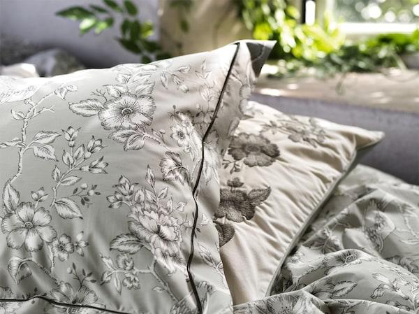 Deux versions des taies d'oreiller IKEA PRAKTBRÄCKA en coton blanc et gris à motifs floraux vintage sur un lit.