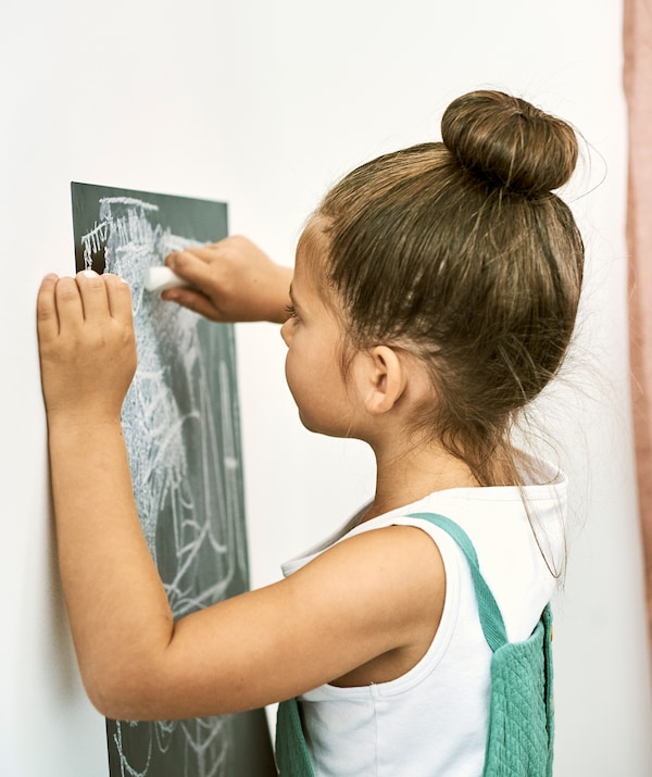 Devojčica crta kredom po zidnoj nalepnici s tablom, nalepljenoj na beli zid.