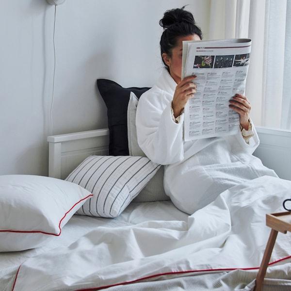 Девушка читает журнал, удобно устроившись на кушетке: ноги укрыты теплым одеялом, под спиной - подушки.